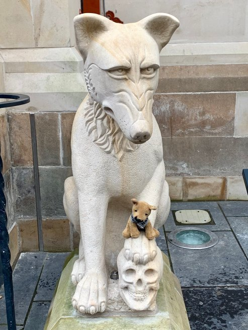The fearless K9 memorial mascot atop a paw of one of the wolves by the entrance to Inverness Town Hall and (Credit: National K9 Memorial Trust)